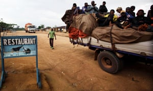 A truck loaded with passengers stops outside a restaurant serving bush meat, in the town of Epulu, Congo in the heart of the Okapi Wildlife Reserve.