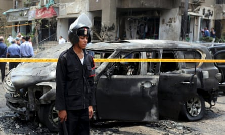 Police investigate the site of a car bomb attack on the convoy of Egyptian public prosecutor Hisham Barakat