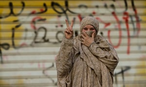A Bahraini pro-democracy protester gestures in front of a wall sprayed with anti-government graffiti.