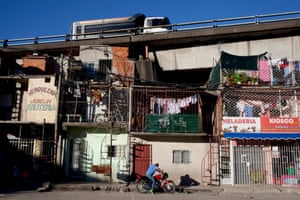 A vehicle drives on a highway over apartments in the Villa 31 neighborhood of Buenos Aires