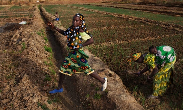 A farmer jumps over a ditch on a bean farm in Heremakono, Mali.