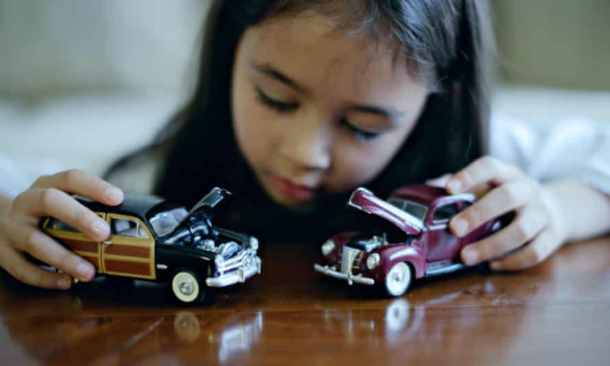 Girl playing with toy cars