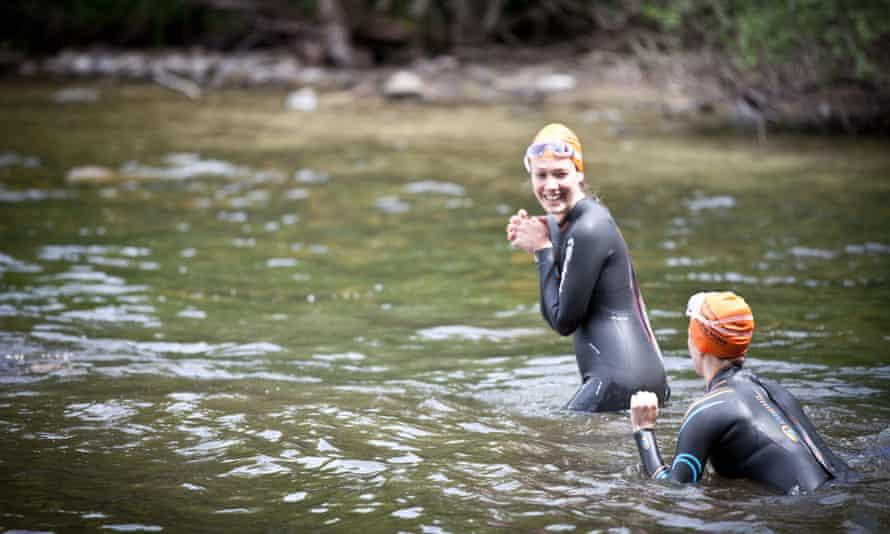 Two women in wetsuits swimming in open water.
