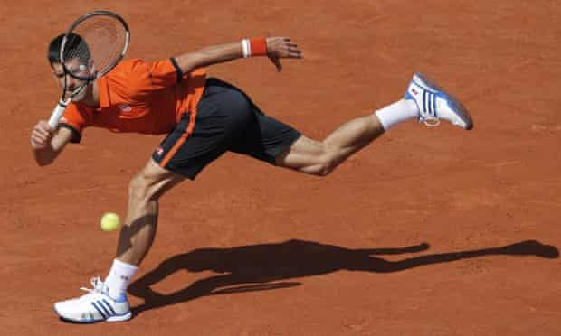 Novak Djokovic returns at full stretch to Rafael Nadal.