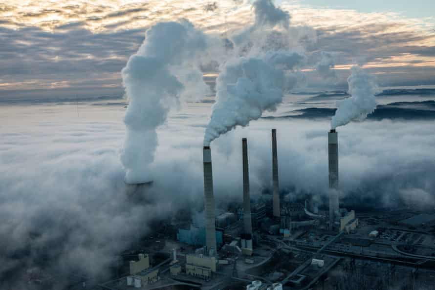 Steam and smoke rise from the cooling towers and chimneys of a power plant in coal-heavy West Virginia.