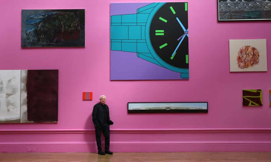 Michael Craig-Martin stands against a Royal Academy wall painted shocking pink under his curatorship surrounded by works selected for this year's Summer Exhibition.