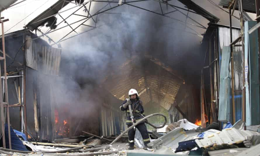 A firefighter extinguishes the fire at a market destroyed after shelling in Donetsk, Ukraine on Wednesday.