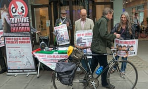 A man takes a leaflet from a protester outside the offices of G4S in May 2014.