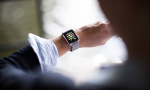 A woman looks at her Apple Watch