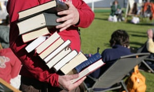 A man at the Hay festival with a pile of books.