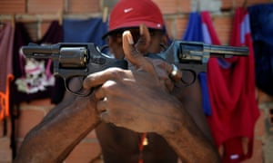 A Brazilian drug gang member nicknamed poses with a gun atop a hill overlooking a slum in Salvador.