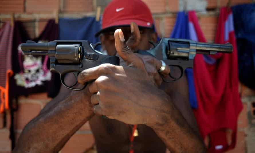 A Brazilian drug gang member nicknamed poses with a gun atop a hill overlooking a slum in Salvador.