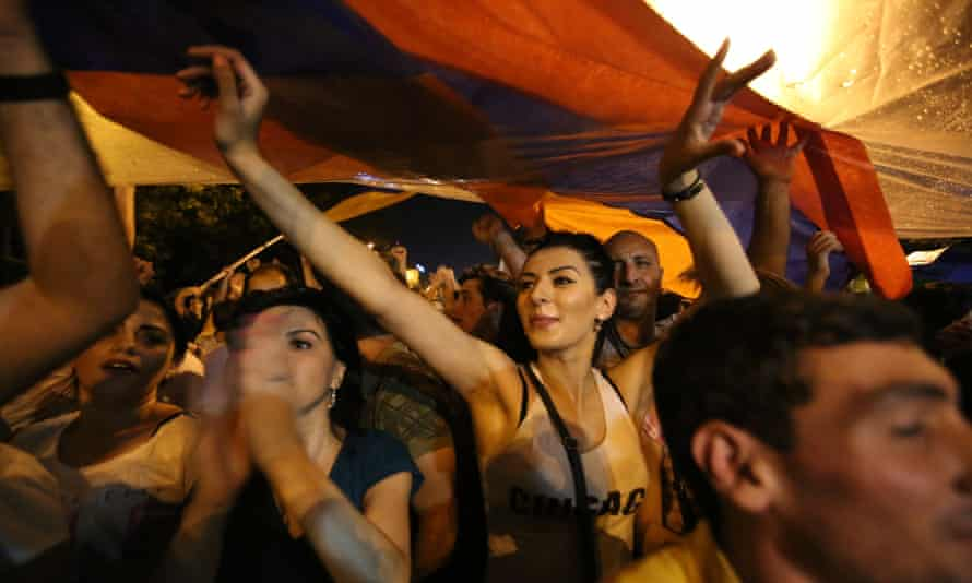 Demonstrators carry a national flag during a protest rally against a hike in electricity prices in Yerevan, Armenia, Saturday, June 27, 2015.