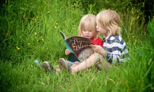 Two young children sitting on grass absorbed in a shared book