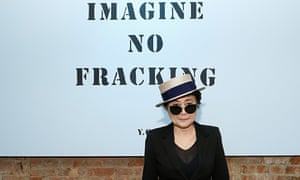 Yoko Ono in a hat and sunglasses in front of a sign reading Imagine No Fracking Installation