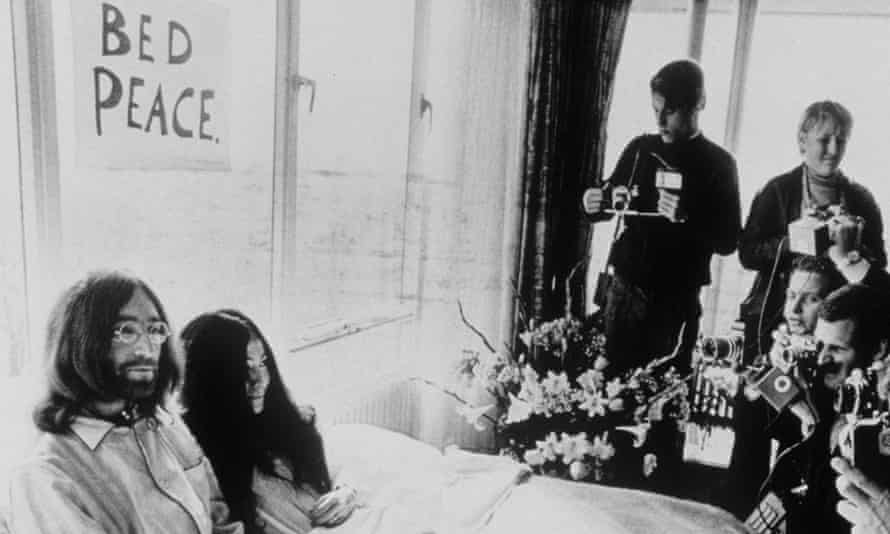 Yoko lying in a bed with flowing hair next to John Lennon, surrounded by photographers, in 1969