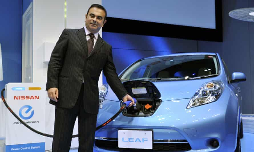 Japan's auto Nissan president Carlos Ghosn charges the electric vehicle 'Leaf' during an announcement of the the company's new mid-term environment plan