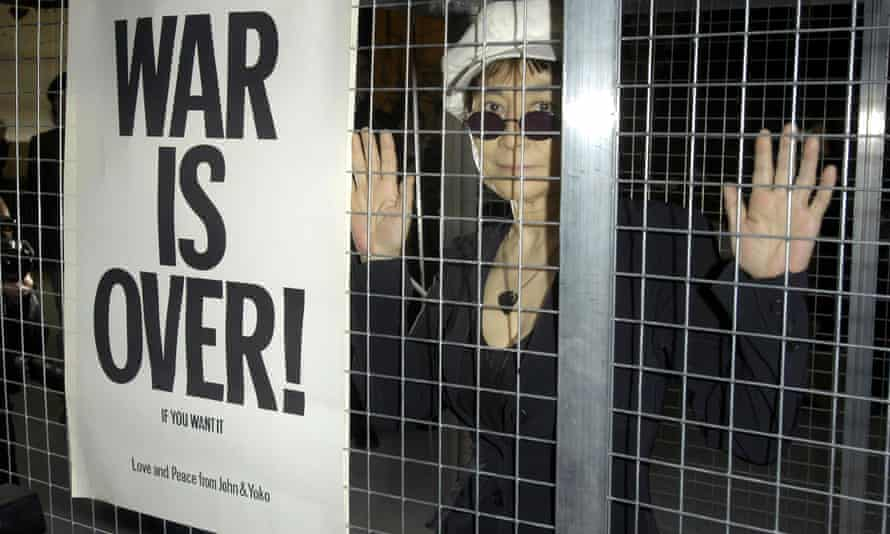 Yoko Ono behind a fence wearing a hat with a sign reading 'War Is Over!' at her exhibition Odyssey of a Cockroach at the ICA, London, in 2004