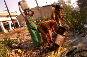 Dalit women collecting human waste from residential dry latrines and emptying the buckets into nearby gutters and streams. 10 Feb 2004