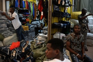 Lamine Ibrahim (left) from Guinea works as his four-year-old son (back, centre) looks on in their shop inside a clothing wholesale market in Guangzhou, provincial capital of Guangdong, 26 August 2013. A lucrative trade between China and Africa has its roots in the low-cost manufacturing base of Guangdong in southern China. Entrepreneurs from across Africa have been drawn here, creating one of the largest black communities in Asia.
