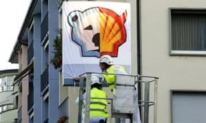 Members of Greenpeace put a banner over the company logo at a Shell gas station during a protest in Zurich this week.
