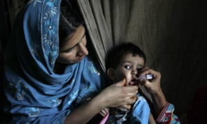 A health worker gives a polio vaccine to a child in Lahore, Pakistan.