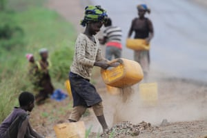 A girl sifts roadside sand to separate the stones to sell as building material in Inchope, northern Mozambique.