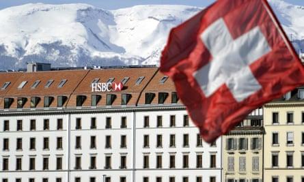 A Swiss flag flies above a HSBC logo is seen on HSBC offices in Geneva, Switzerland.