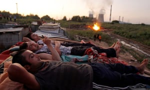 Migrants workers from Tajikistan relax on the roof of their shelter after working at local market outside Moscow.
