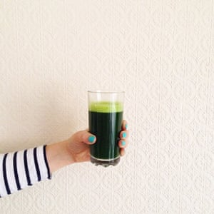 Hand holding glass of green juice