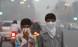 Children cover their faces against air pollution in New Delhi, India.