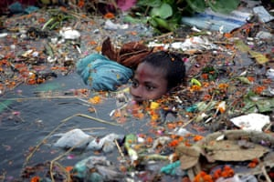 A boy swims through floating debris in the river Yamuna in New Delhi, India.
