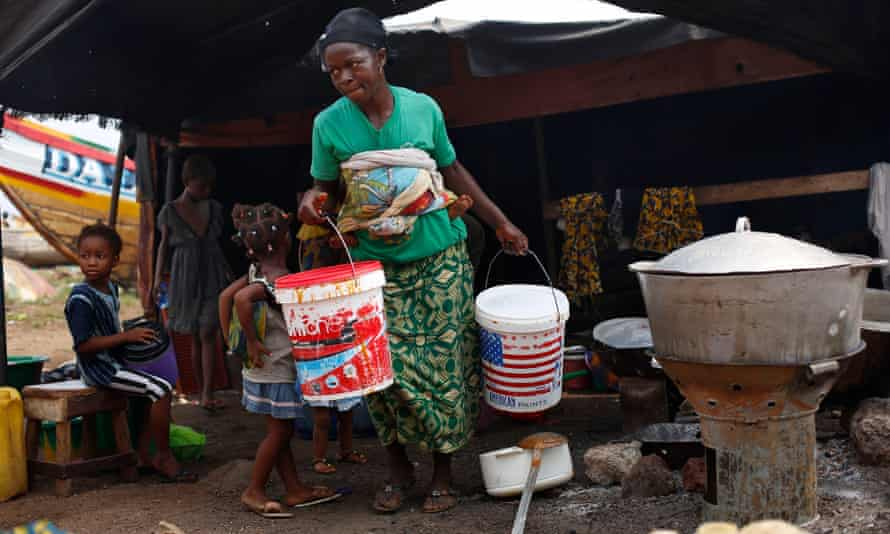 A woman carries buckets at the fishing port of Conakry, Guinea, in November 2014. A new study finds women's contribution to health and wellbeing of families and communities is undervalued worldwide.