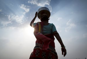 Bhaagi carries an empty metal pitcher as she walks to fetch water from outside her village