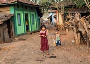 Children walk near a general store in Denganmal