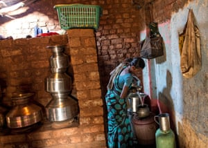 Shivarti empties a pitcher before she gets ready to get water from a well