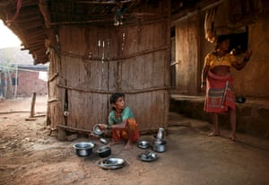Sakhri (L), Bhagat's second wife, listens to Tuki, his first wife, as she washes utensils outside their house