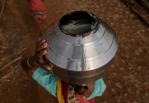 Bhaagi, the third wife of Sakharam Bhagat, carries a metal pitcher filled with water
