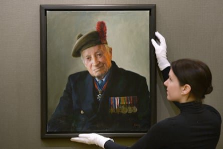 A gallery assistant with a portrait of Capt Brian Stewart by Paul Benney at the exhibition The Last of the Tide.