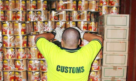 A customs official inspects tins of tomato shipped to Australia  that contained 4.4 tonnes of ecstasy tablets.