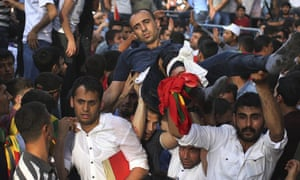 Supporters carry a wounded man at a Kurdish Peoples' Democratic Party rally in Diyarbakir.