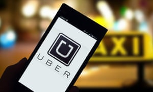 A mobile phone user looks at a logo of taxi-hailing app Uber on his smartphone .