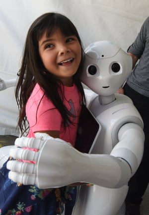 Yaretzi Bernal, six, gets a hug from Pepper the 'social' robot.