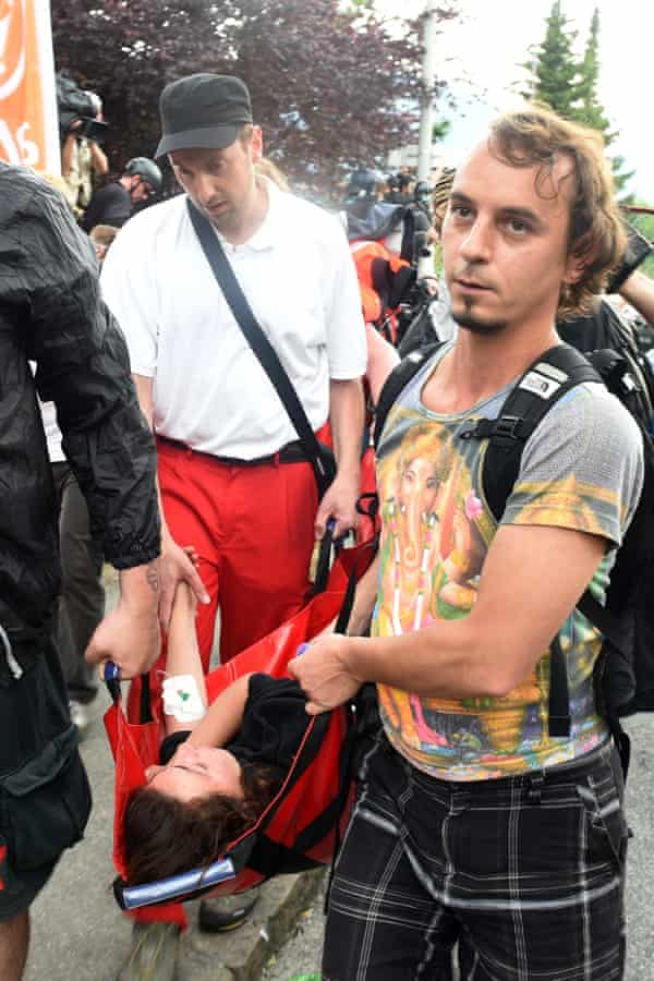 An injured protester is carried away in Garmisch-Partenkirchen after scuffles between activists and riot police.