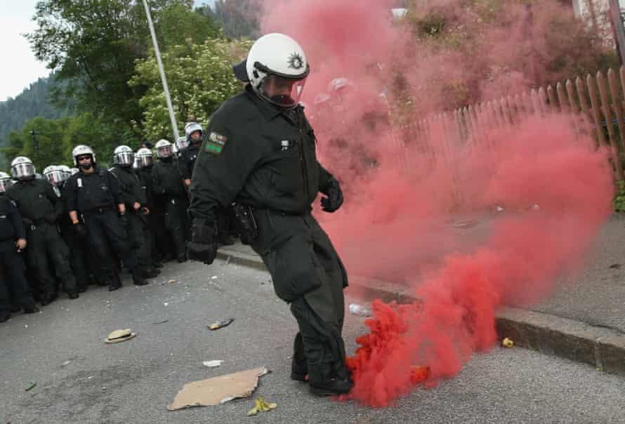A policeman kicks away a smoke bomb during scuffles during a march by anti-G7 protesters through Garmisch-Partenkirchen.