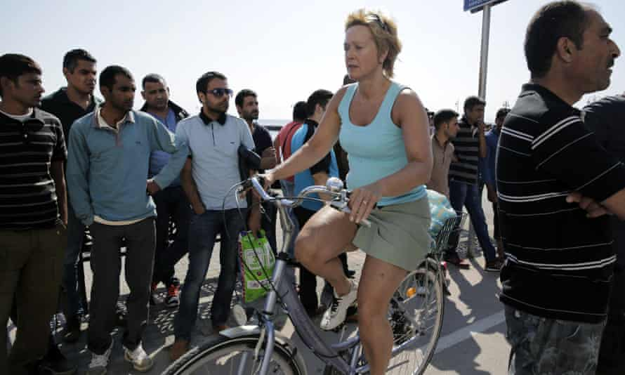 A tourist rides her bicycle past migrants waiting outside the police station.