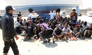 Migrants sit on the ground after being detained by Libyan coast guard