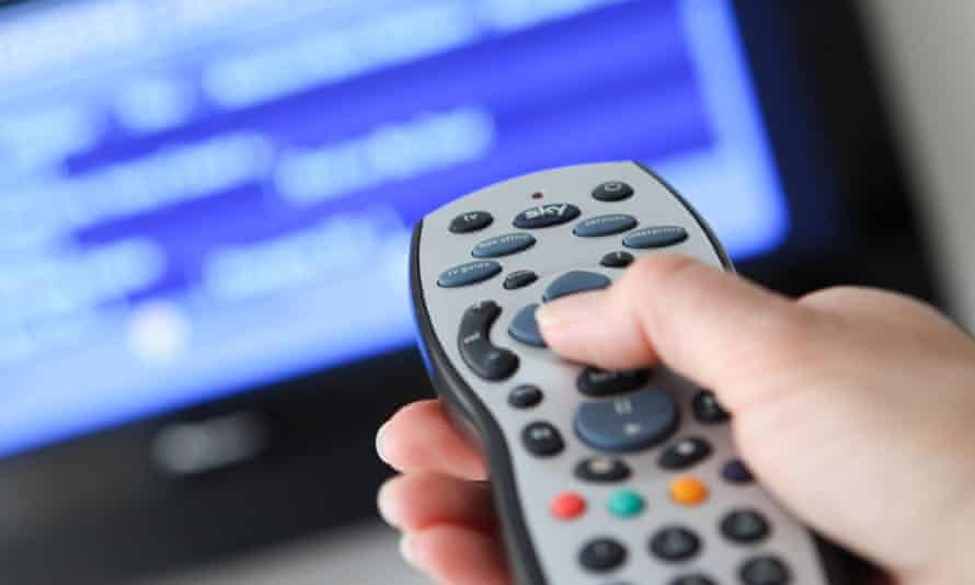 A woman uses a Sky remote control, whose pause button works better than the climate's.