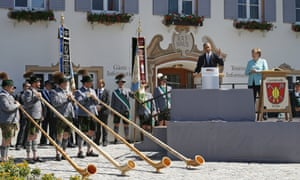Alpine horn players stand before Barack Obama as he and Angela Merkel speak in the Bavarian village of Krün.