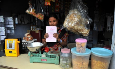 A woman poses with her microfinance 'loan recovery book' at her shop in Hyderabad, India